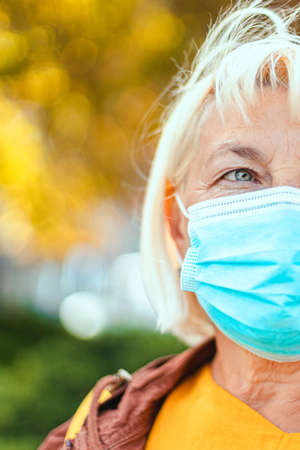 Caucasian woman 50 years old in a protective medical mask looks away in an autumn park. Safety in public place during virus outbreak.