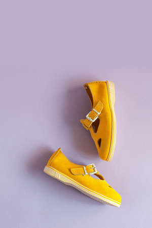 Womens summer yellow sandals on lilac background with copy space. Vertical photo. View from above. 版權商用圖片