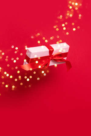 Pink gift box with red ribbon decoration in the air on a red background. Christmas and New Year holiday background.