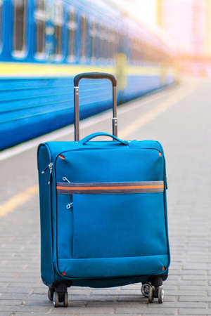 Hand luggage on the platform near the train carriage. Blue suitcase for travel and leisure. Vertical photo 版權商用圖片