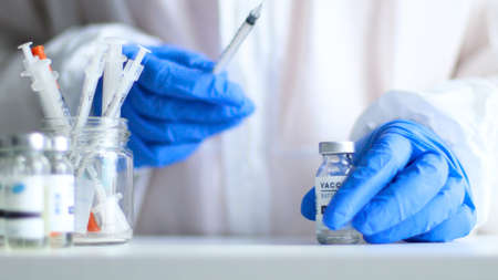 Nurse or doctor in medical protective uniform and latex rubber gloves holding syringe with vaccine while preparing for work during virus, flu or measles pandemic for poster, web banner, article or advertisement
