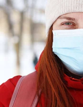 Young Caucasian woman wearing medical mask looking to the camera at street of city. Safety in public place during outbreak. 版權商用圖片