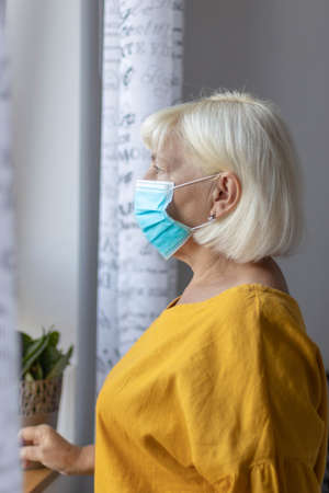 Caucasian woman 50 years old in a protective medical mask looking out the window while sitting at home or a hospital on the carine during the pandemic.