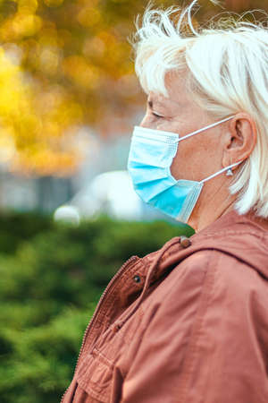 Side view of caucasian woman 50 years old in a protective medical mask looks away in an autumn park. Safety in public place during outbreak.
