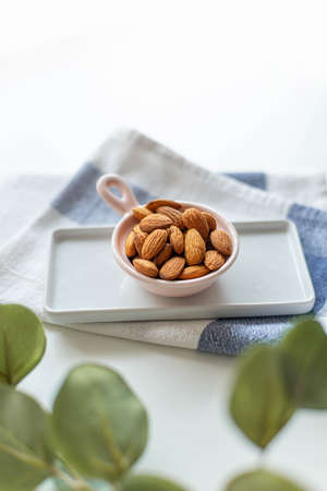 Fresh nut almonds in a ceramic bowl with towel on a white background, vertical photo. Green plant in the foreground