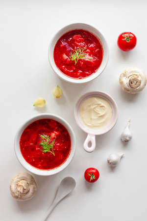 Top view of the traditional Ukrainian borscht or soup with beets, potatoes, tomatoes, meat in bowls on white background. Top view. Free copy space.