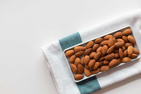 Fresh nut almonds in a ceramic bowl with towel on a white background. Flat lay, top view, copy space.