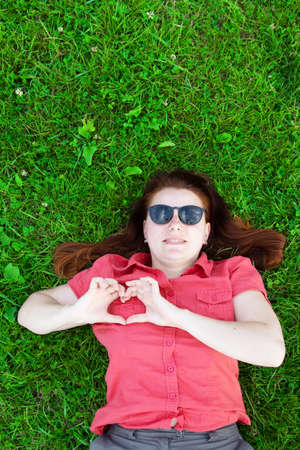 Relaxed woman lying on the grass. Young caucasian girl in sunglasses shows love heart sign with her hands