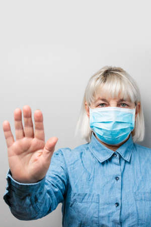 Caucasian woman 50 years old in a protective medical mask shows hand stop sign on gray background 版權商用圖片
