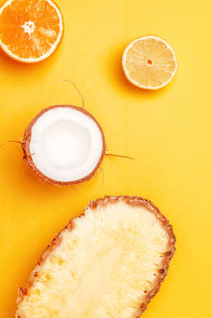 Assorted exotic fruits on a bright yellow background. Half lemon, orange, pineapple and coconut. Top view, vertical, flat lay 版權商用圖片