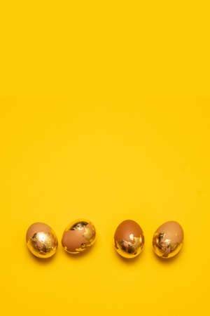 Golden Easter eggs on yellow background with copy space. Flat lay 版權商用圖片