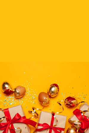 Easter easter eggs with gift boxes on bright yellow background. Flat lay, top view, mockup, overhead, template