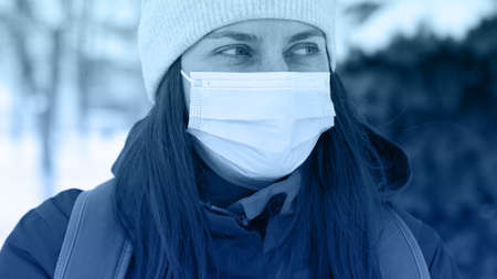 Young Caucasian woman wearing a medical mask at street of city in winter time. 版權商用圖片