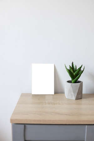 White empty paper blank frame mockup on home wooden table. Modern grey concrete flowerpot with succulent plant. White wall background