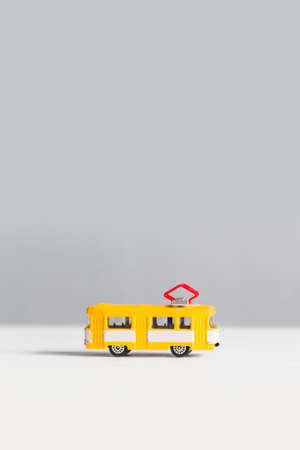Yellow trackless trolley model toy on white gray background with copy space. Vertical photo 版權商用圖片