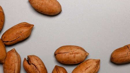Assorted pecan nuts in shell on gray background with copy space 版權商用圖片