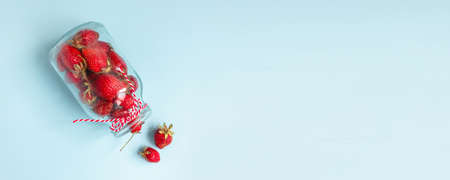 Summer fresh strawberry berry fruits in jars on blue background. Organic ingredients. Flat lay, top view