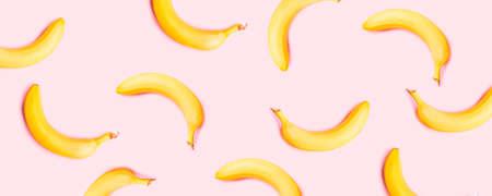 Ripe banana falling in the air on minimal pink background. Minimal creative art
