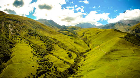 Scenic panoramic view of nature green rolling hills landscape capped Mount Kazbek mountain peaks of Georgia in the background on a beautiful sunny summer day Banque d'images