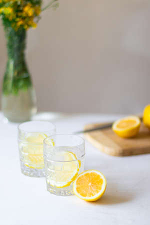 Homemade refreshing summer lemonade drink with lemon slices and ice in glasses with flowers bouquet in a vase on the background Banque d'images