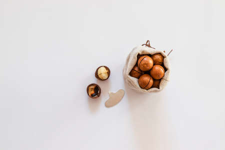 Raw macadamia nuts in canvas bowl on a white solid background. Minimal flat composition