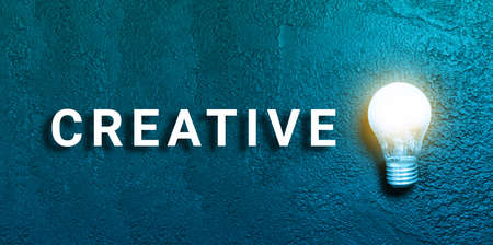Creative text and idea illuminated light bulb on a dark grunge background. Creative inspiration, planning ideas concept. Flat lay, top view, copy space