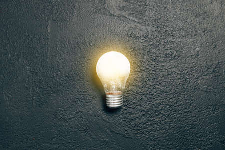Bright idea glowing light bulb a dark grunge background. Creative inspiration, planning ideas concept Banque d'images - 167115944