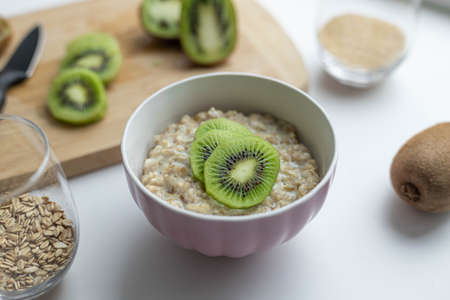 Oatmeal with kiwi and honey in a white bowl on a table. Healthy breakfast, diet food Banque d'images