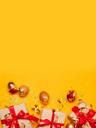 Top view of holiday card with gold brown eggs and gift boxes with red ribbon bow and glitter confetti on a yellow background.Happy easter.