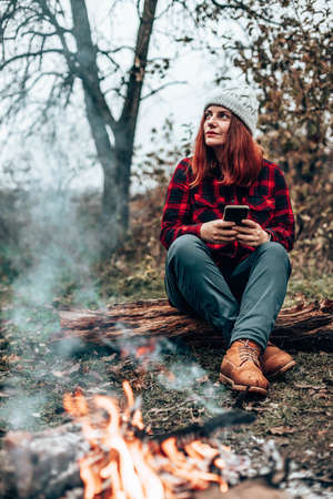 Traveler girl in hipster clothes sits on a log in the forest near the campfire by camping. Woman using smartphone in nature