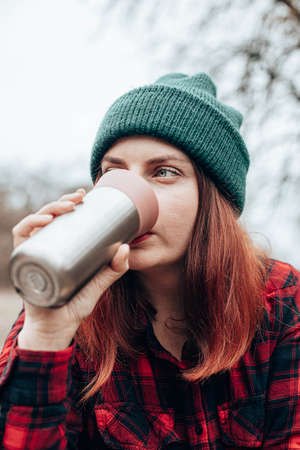 Caucasian woman drinks from a mug of flask. Rest at in nature autumn forest