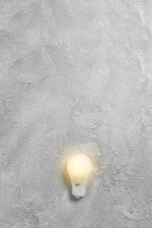 Bright idea illuminated light bulb on grey background. Creative inspiration, planning ideas concept. Flat lay, top view with copy space