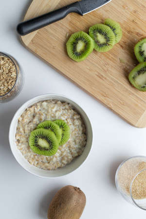 Oatmeal with kiwi and honey in a white bowl on a table. Tasty and healthy breakfast. Flat lay, top view, copy space.