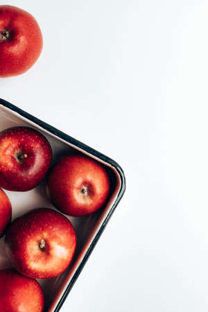 Fresh ripe red apples in enamel container and on the table. Flat lay, top view, copy space