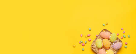 Festive basket with colored Easter eggs and tasty colored Candy jelly beans on a yellow background with copy space, top view, flat lay. Horizontal photo
