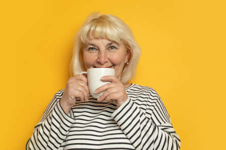 Cheerful young blonde haired woman drinking tea or coffee on a yellow background at the morning Zdjęcie Seryjne