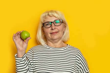 Cheerful old blonde haired woman hold a green apple on a yellow background