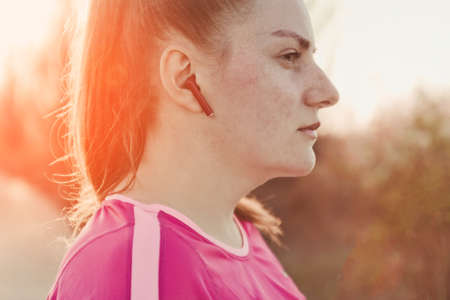 girl with wireless headphones runs along the trail in the rays of sunlight. Weight loss concept Zdjęcie Seryjne