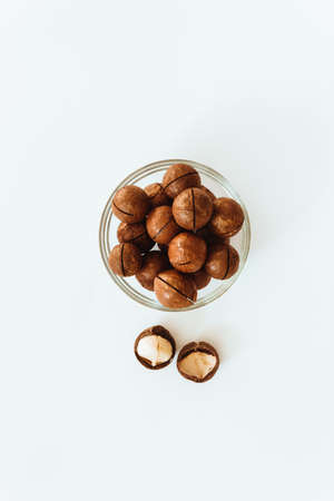 Raw macadamia nuts in a transparent glass bowl and scattered on grey solid background. Minimal composition.