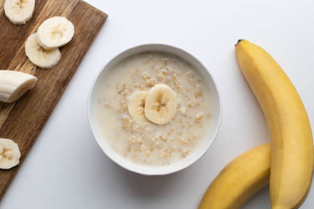 Bowl of oatmeal porridge with banana on white table for healthy breakfast