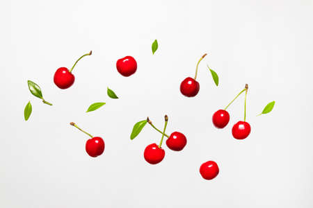 Ripe cherry berry with green leaves levitating on white background. Berry summer background. Flat lay, top view, copy space