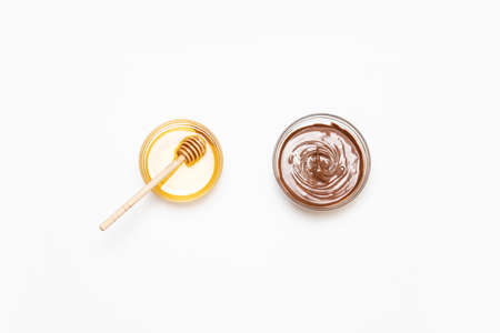 Fresh honey and glass jar with tasty chocolate cream on white background, top view