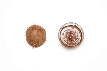 Composition with half coconut and glass jar with tasty chocolate cream on white background, top view