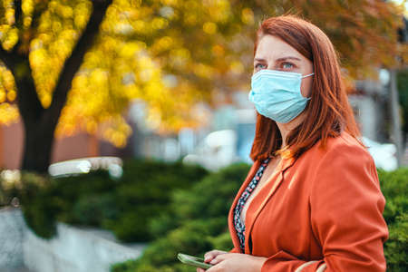 Businesswoman with safety mask standing in the city. Beautiful young girl with red hair in a protective medical mask against allegria, virus