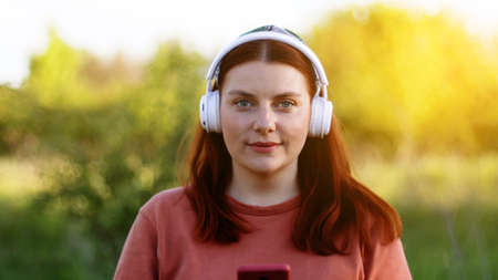 Attractive happy girl listening to music with headphones. Student using mobile phone, having video chat
