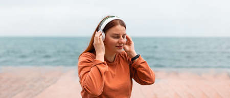 Close up portrait of beautiful girl listening music with headphones on sunny day Banque d'images