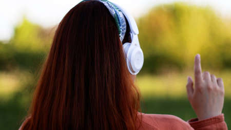 Back view of caucasian young woman listening music with headphones on sunny day while walking in city park