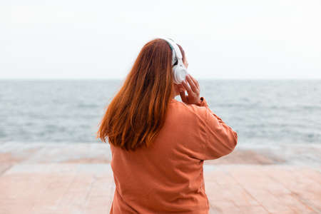 Close up portrait of young girl meditates with wireless headphones outdoors on beach looking the sea Banque d'images