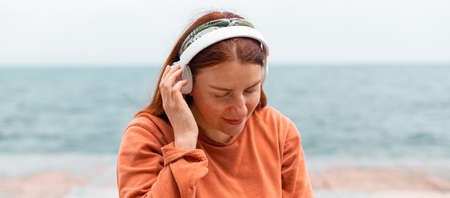 Beautiful caucasian young woman listening music with headphones on sunny day while walking near the sea