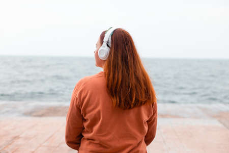 Back view of foxy hair woman wearing headphones listening music or podcast from smartphone application against the sea